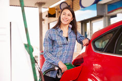 Woman man refuelling a car at a petrol station Royalty Free Stock Image