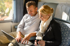 Woman and man relaxing in train laptop Stock Photos