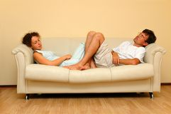 Woman and man repose on the white sofa Stock Images