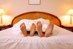Woman and man rest on soft big bed Stock Images