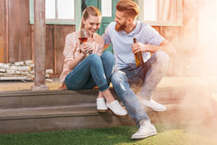 Woman and man resting with beer and wine on porch. Attractive women and men resting with beer and wine on porch Stock Images