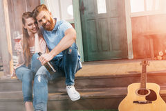 Woman and man resting with beer and wine on porch. Attractive women and men resting with beer and wine on porch Royalty Free Stock Image