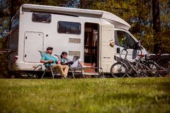 Woman with a man resting near motorhomes in nature. Family vacat Stock Photography