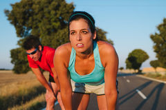 Woman and man resting after running road race. Athletes taking a rest after road running race or marathon. Tired female runner and men resting and breathing Stock Photo
