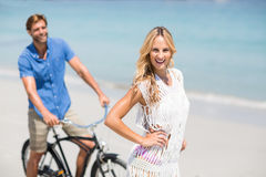Woman by man riding bicycle at beach Stock Image