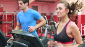 Woman and man running on a treadmill. In gym stock video