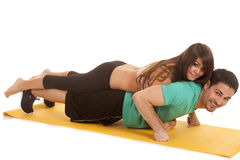 Woman on man's back pushup both looking Royalty Free Stock Photography