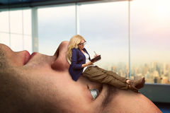 Woman on the man's face. Businesswoman analyst is lying on the client's face royalty free stock photo