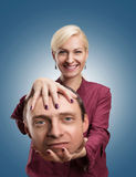 Woman with man's head in her hand. Happy analyst with client's head in her hand stock image
