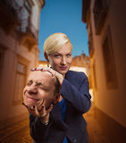 Woman with man's head in her hand Stock Photo