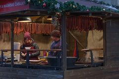 Woman and man sale sausage at Christmas market stock images