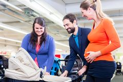 Woman, man, and sales lady in baby store royalty free stock photo