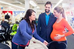 Woman, man, and sales lady in baby store royalty free stock image