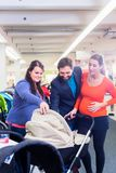 Woman, man, and sales lady in baby store stock images