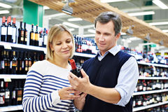 Woman and man selected bottle of wine in store Royalty Free Stock Photos