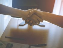 Woman and Man shaking hand over office table in bright orange light stock images
