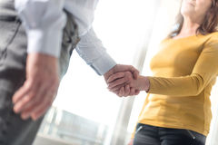 Woman and man shaking hands in office Stock Images