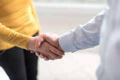 Woman and man shaking hands in office stock photography