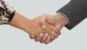 A woman and a man shaking hands stock image
