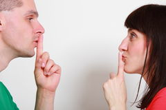 Woman and man showing hand silence sign stock photos
