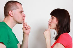 Woman and man showing hand silence sign Royalty Free Stock Photo