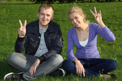 Woman and man showing victory sign. Woman and men showing victory sign in outdoor Stock Photo