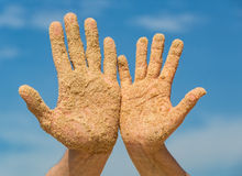 Woman and Man Shows his Open Hands Covered with Beach Sand Royalty Free Stock Images