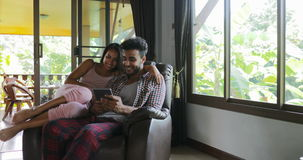 Woman And Man Sitting In Armchair Using Tablet Computer Talking Touch Screen Browsing Online Internet, Young Couple At. Home Together Slow Motion 60 stock video footage