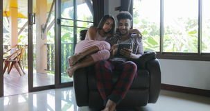 Woman And Man Sitting In Armchair Using Tablet Computer Talking Touch Screen Browsing Online Internet, Young Couple At. Home Together Slow Motion 60 stock video