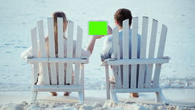 Woman and man sitting on the beach and looking at. Young couple sitting back in the wooden chaise-longues on the beach. They holding tablet computer with green stock video