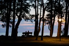 A woman and a man sitting on a bench and meeting the sunset on the beach stock photo