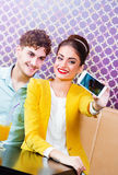 Woman and man sitting at cafe, taking a selfie Stock Photos