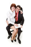 Woman and man sitting on a chair with a notebook. Young, smiling, woman and man sitting on a chair with a notebook, isolated on a white background Royalty Free Stock Image