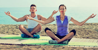 Woman and man sitting cross-legged do yoga poses on beach Royalty Free Stock Photos