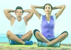 Woman and man sitting cross-legged do yoga poses on beach Royalty Free Stock Image