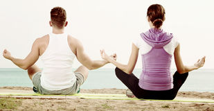 Woman and man sitting cross-legged do yoga poses on beach Royalty Free Stock Photography