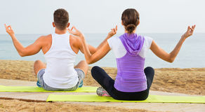 Woman and man sitting cross-legged do yoga poses on beach Royalty Free Stock Photo