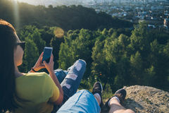 Woman with man sitting on the top of the hill injoy view on sunset Stock Photo