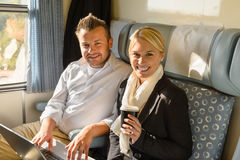 Woman and man sitting in train smiling Stock Images