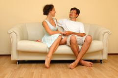 Woman and man sitting on the white sofa. Young woman and man sitting on the white sofa Stock Photography