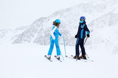 Woman and man skiers turn in mountains Royalty Free Stock Photos
