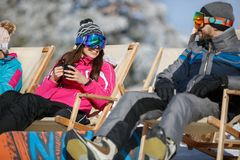Woman and man on skiing in sunbed. Woman and men on skiing in sunbed resting and refreshing Royalty Free Stock Photography