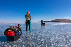 A woman and a man with a sledge and trekking pole is ice of Baik Royalty Free Stock Photo