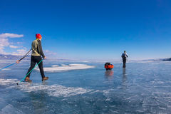 A woman and a man with a sledge and trekking pole is ice of Baik Stock Image