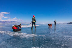 A woman and a man with a sledge and trekking pole is ice of Baik Stock Photo