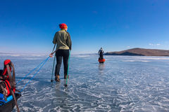 A woman and a man with a sledge and trekking pole is ice of Baik Stock Photography