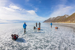 Woman and a man with a sledge and trekking pole is ice of Baikal Stock Photos