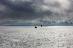Woman and a man with a sledge and trekking pole is ice of Baikal Royalty Free Stock Photos