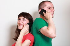 Woman and man with smile talking on mobile phone Royalty Free Stock Photography
