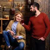 Woman and man on smiling faces enjoy cozy atmosphere with hot drinks. Couple spend pleasant evening, interior background. Woman and men on smiling faces enjoy Royalty Free Stock Images